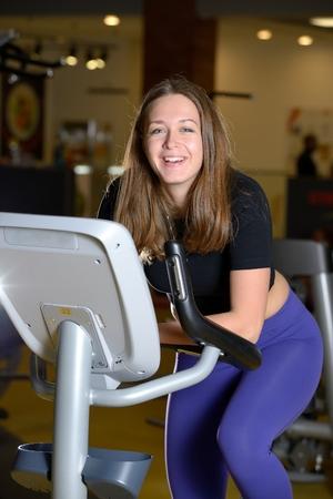 cardiovascular exercising: Smiling woman training on exercise bike