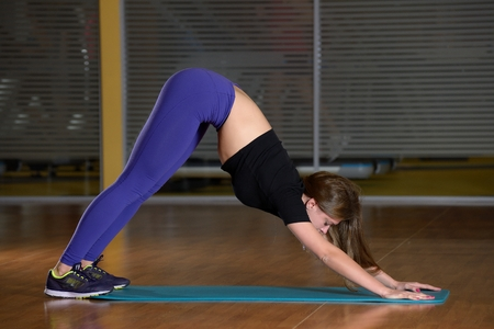 exersice: Beautiful girl does exercise on an extension on blue mat in gym