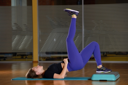 musculine: Sporty girl doing exercise on platform for an aerobics step