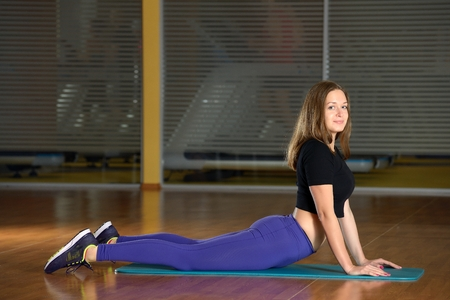 Beautiful girl does exercise on an extension on blue mat in gym