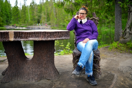 sits on a chair: Beautiful woman sits on fairytale chair near table in wood at lake Stock Photo