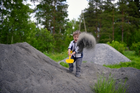 throws: Little boy plays on heap of crushed stone Stock Photo