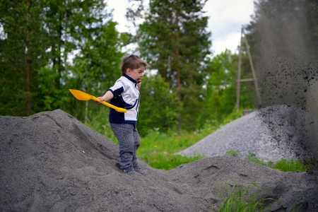 plays: Little boy plays on heap of crushed stone Stock Photo