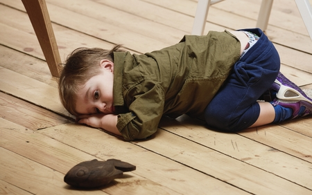 sorrowful: Sorrowful little boy on floor