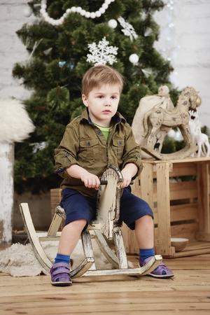 juguetes de madera: Pequeño paseo muchacho madera caballo mecedora delante del árbol de navidad
