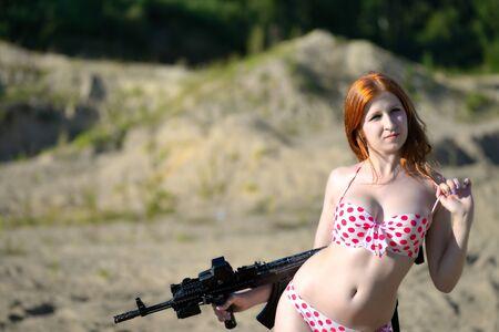 militaire sexy: femme sexy habillée en maillot de bain avec un pistolet en plein air