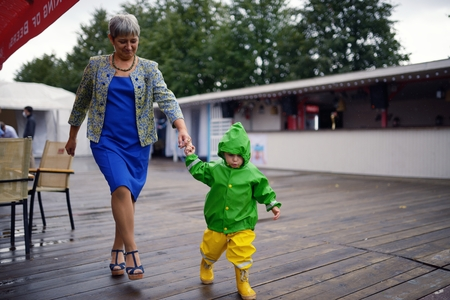 wet clothes: Happy little boy in not getting wet clothes together with grandmother Stock Photo