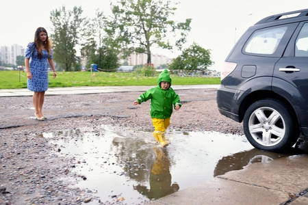 wet clothes: Happy little boy in not getting wet clothes plays in pool on street with mother Stock Photo