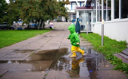 wet clothes: Happy little boy in not getting wet clothes plays in pool on street