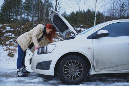 chica joven pelirroja mira debajo de la capucha del coche roto en el camino rural