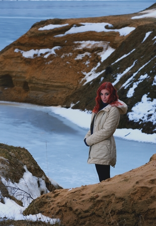 stays: Beautiful redhead girl stays against Nordic landscape