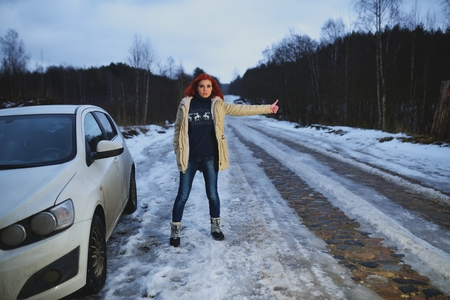 hitchhiking: Beautiful redhead woman hitchhiking by broken car