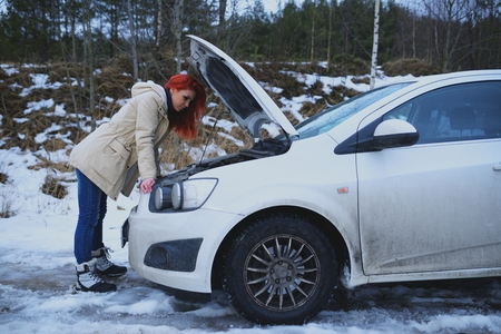 cowl: Young redhead girl looks under cowl of broken car on rural road