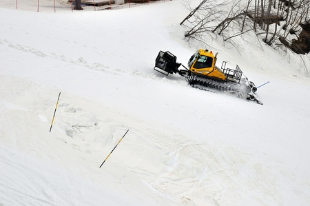 snow grooming machine: Yellow ratrak works in mountains Stock Photo