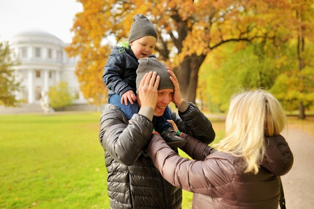 corrects: Wife corrects clothes for husband with child on a shoulders in park Stock Photo