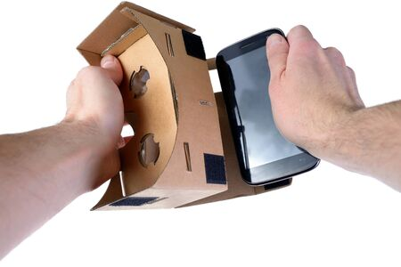 Male hands insert mobile phone into VR glasses cardboard