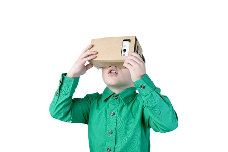Little child uses virtual reality (VR cardboard) isolated on white background Фото со стока