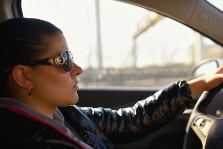sunglassess: Woman wearing sunglasses drives car and is concentrated looks at road