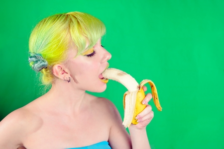 banana: Beautiful girl with green hair eat banana on green background Stock Photo