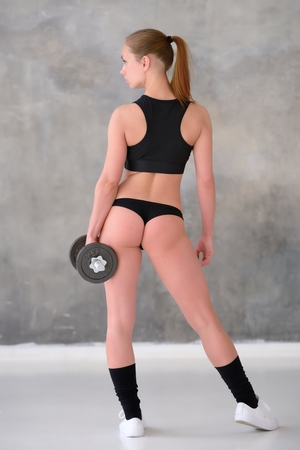 Beautiful young girl with an ideal figure and dumbbell in hand