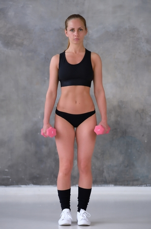 Beautiful young girl with an ideal figure and dumbbell doing exercises