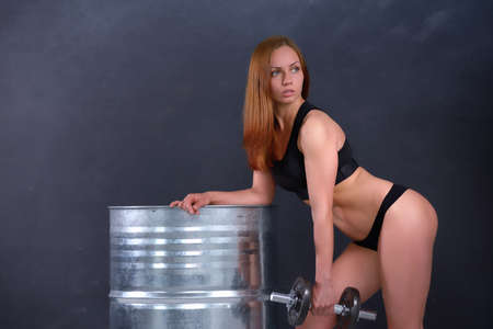 leans on hand: Beautiful young girl with an ideal figure and dumbbell in hand leans the elbows on barrel