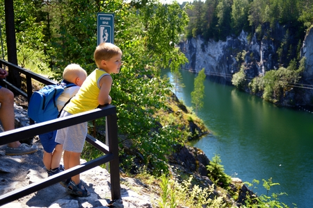 Two small childrens look through a handrail at a canyon