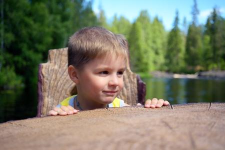 sits on a chair: Portrait of a cute boy sits chair near edge of a river