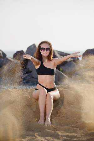 fulfilling: Young woman sitting and throwing sand in air
