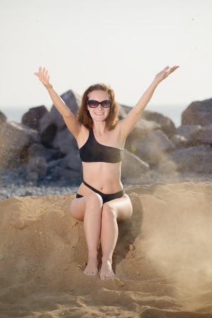 Junge Frau sitzt und Sand in der Luft zu werfen