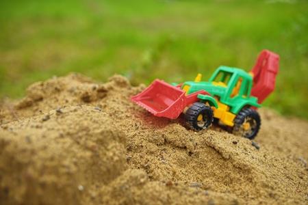 Children toy tractor in sandbox