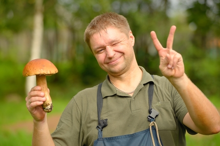 picker: The happy mushroom picker holds cepe in hand