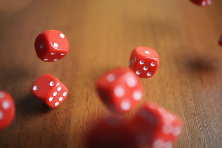 several: Several rolling red dice fall on a table