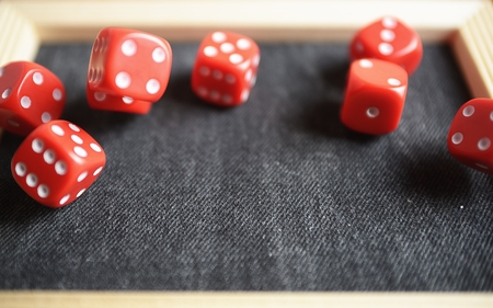 Several rolling red dice fall on special boardgame frame