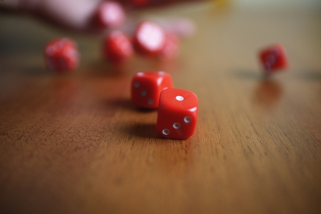 rolling dice: Several rolling red dice fall on a table
