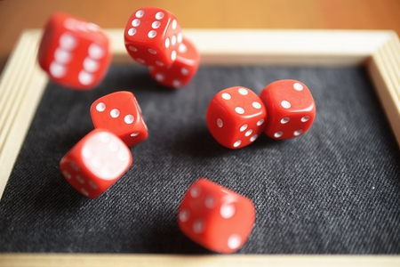rolling dice: Several rolling red dice fall on special boardgame frame