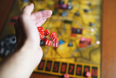 rolling dice: Several rolling red dice fall on a table with boardgame. Gameplay moments