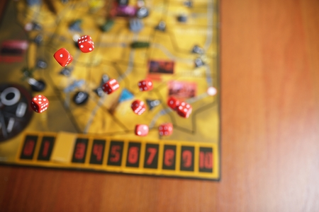 gameplay: Several rolling red dice fall on a table with boardgame. Gameplay moments