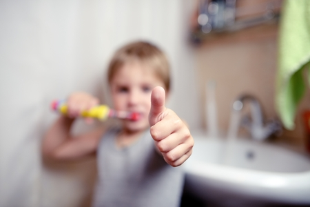 toothbrushing: Little boy brushing teeth in bath with electric brush also shows thumbs up