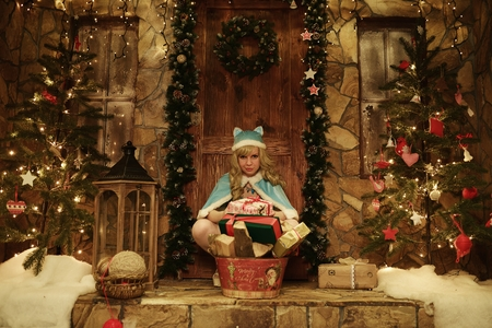 snegurochka: Snow Maiden with presents on doorstep of house decorated in Christmas style