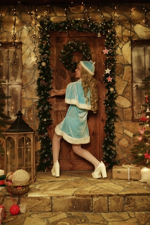 snegurochka: Snow Maiden on doorstep of house decorated in Christmas style try to open door