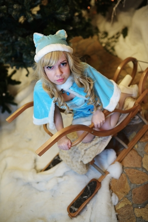 Beautiful Snow Maiden in studio Christmas interior sits on sledge Stock Photo