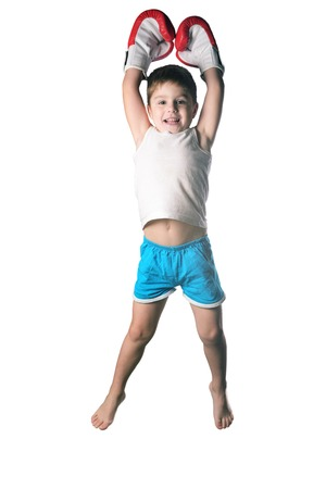 Little boy with red boxing gloves victory jump on white background isolated