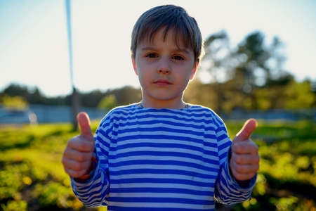 Portrait of dirty little boy in village with thumbs up photo