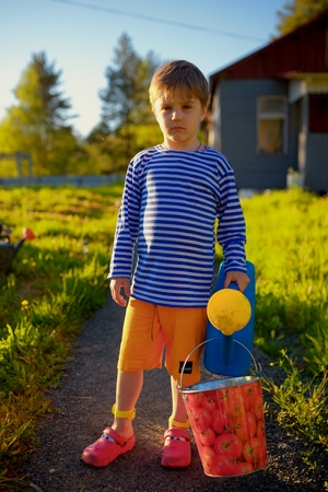 Portrait of little boy with watering can in garden at summer day photo