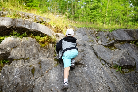 Young caucasian child boy climbing rocks in forest