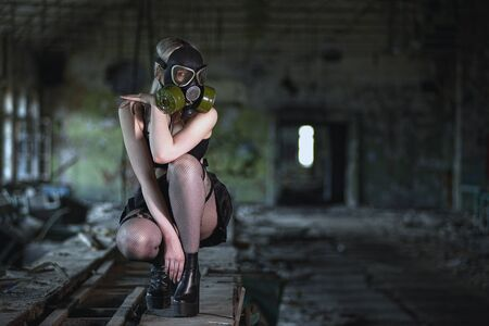 Beautiful, young girl post apocalypse girl sits in abandoned factory with gas mask Фото со стока