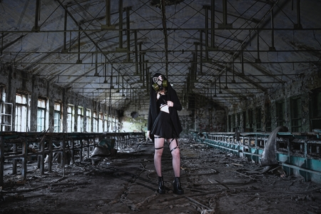 Beautiful, young girl post apocalypse girl stand in abandoned factory with gas mask