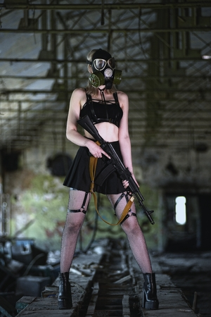 Beautiful, young girl post apocalypse girl stand in abandoned factory with gas mask and machine gun