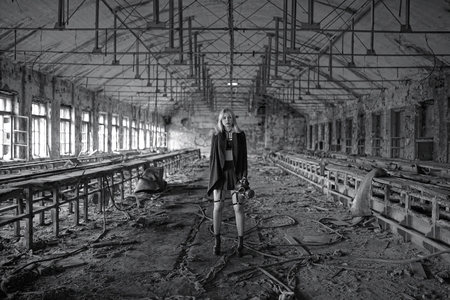 Beautiful, young girl post apocalypse girl stand in abandoned factory Фото со стока